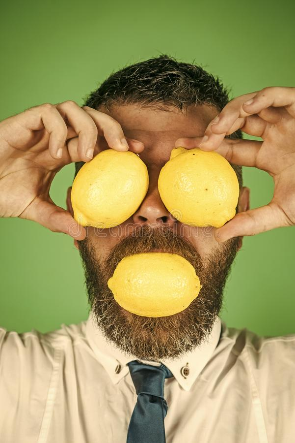 Healthy eating. Vegetarian, health and wellbeing. Vitamin citrus at hipster on green background. Man with long beard eat lemon. Dieting and fitness. Fruit and royalty free stock photo