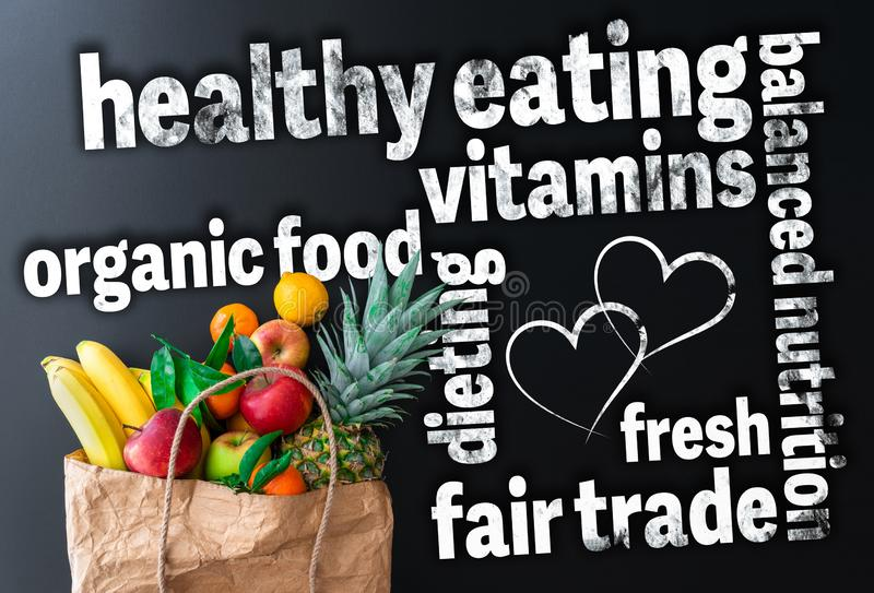 Healthy eating word cloud with paper bag filled with fresh organic fruits stock photo