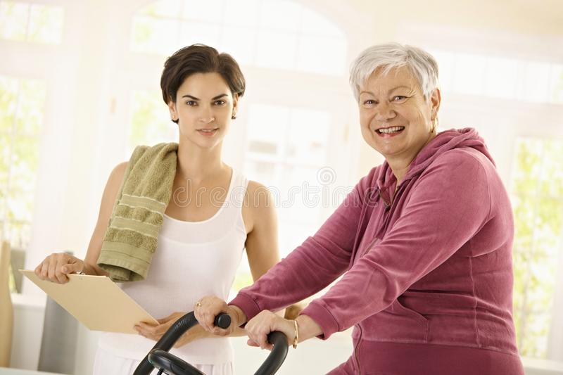 Healthy elderly woman on exercise bike royalty free stock image