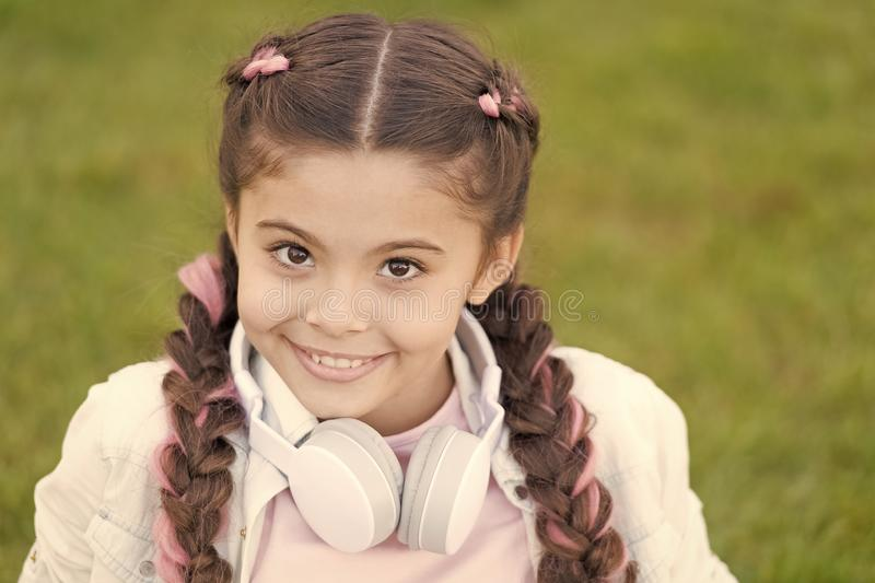 Healthy emotional happy kid relaxing outdoors. What makes child happy. Girl braids hairstyle and modern headphones enjoy. Relax. Secrets to raising happy child stock image