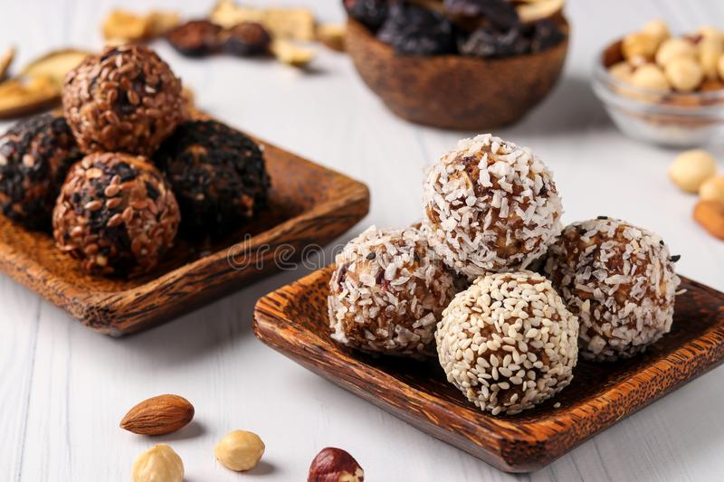 Healthy energy balls of nuts, oatmeals and dried fruit with coconut, flax and sesame seeds on wooden coconut plates on a white stock photos