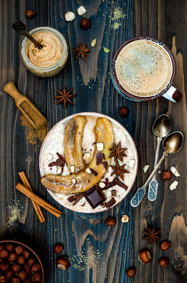 Healthy fall and winter breakfast bowl. Chai tea infused overnight oats porridge topped with caramelized bananas, raw dark stock image