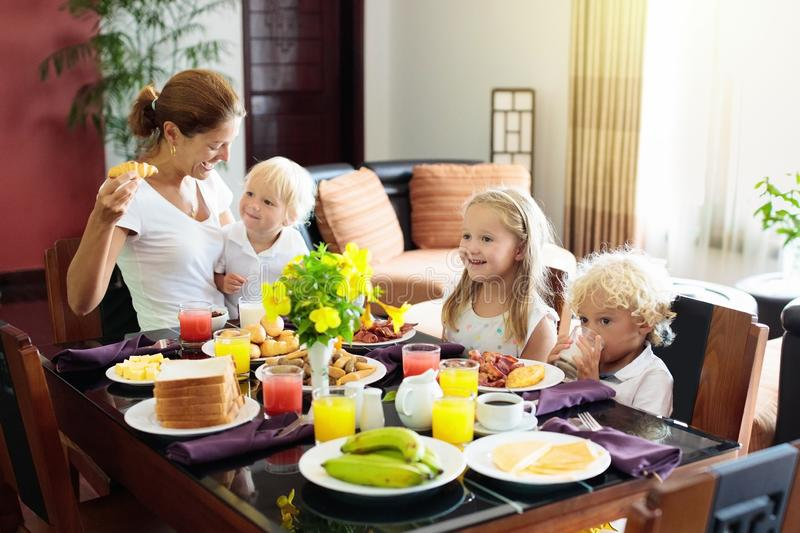 Healthy family breakfast for mother and kids. Healthy family breakfast at home. Mother and kids eating tropical fruit, toast bread, cheese and sausage. Children stock image