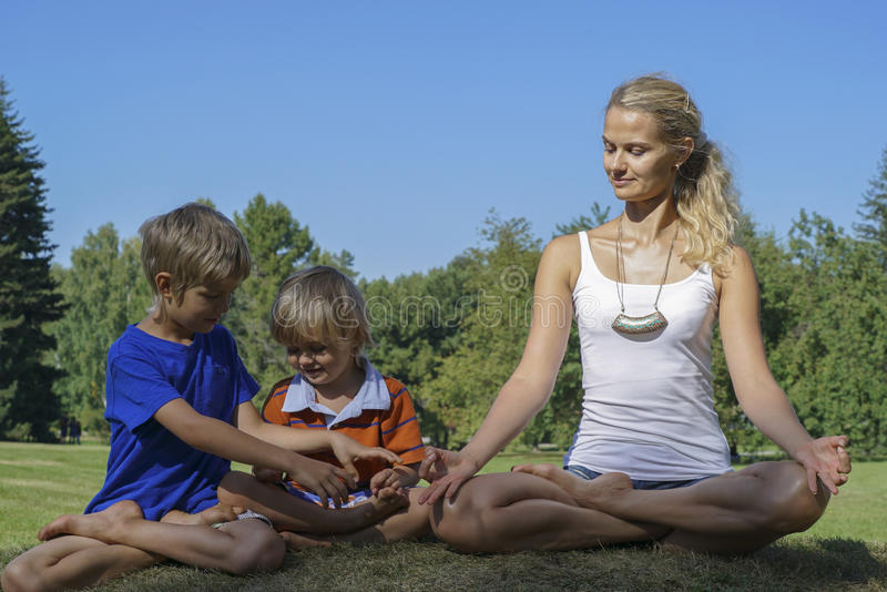 Healthy family doing yoga in the park. Older brother teaches younger how to sit in the Lotus position royalty free stock photos