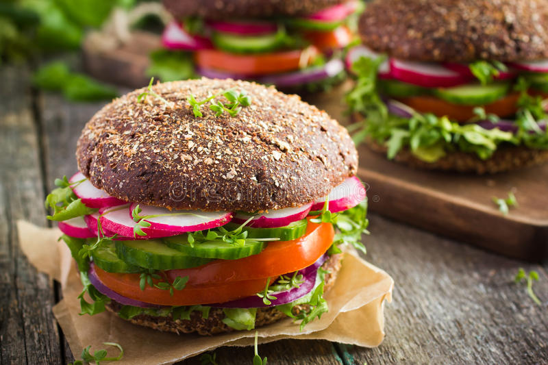 Healthy fast food. Vegan rye burger with fresh vegetables. On old wooden background stock photo