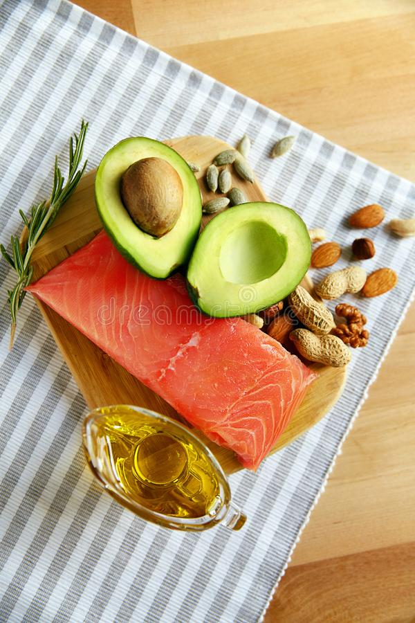Healthy Fats. Fresh Organic Food On Table. Close Up Of Avocado, Nuts, Olive Oil And Salmon Fillet Lying On Wooden Cutting Board In Kitchen. Food Ingredients stock image