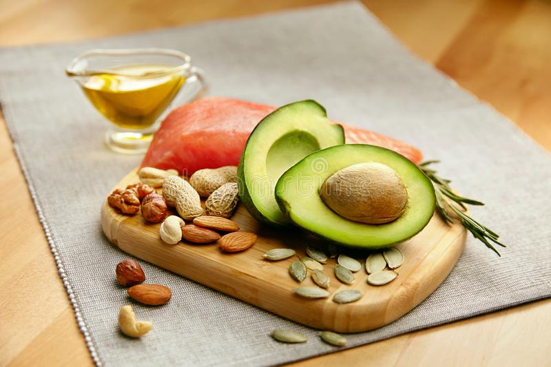 Healthy Fats. Fresh Organic Food On Table. Close Up Of Avocado, Nuts, Olive Oil And Salmon Fillet Lying On Wooden Cutting Board In Kitchen. Food Ingredients royalty free stock image