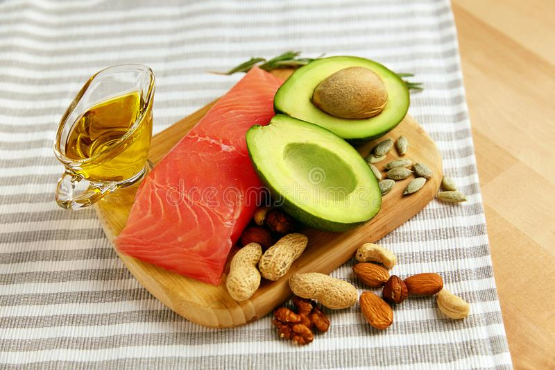 Healthy Fats. Fresh Organic Food On Table. Close Up Of Avocado, Nuts, Olive Oil And Salmon Fillet Lying On Wooden Cutting Board In Kitchen. Food Ingredients royalty free stock images