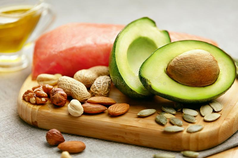 Healthy Fats. Fresh Organic Food On Table. Close Up Of Avocado, Nuts, Olive Oil And Salmon Fillet Lying On Wooden Cutting Board In Kitchen. Food Ingredients stock photo