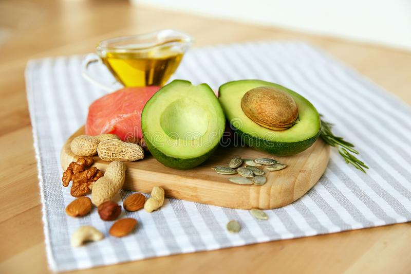 Healthy Fats. Fresh Organic Food On Table. Close Up Of Avocado, Nuts, Olive Oil And Salmon Fillet Lying On Wooden Cutting Board In Kitchen. Food Ingredients stock images