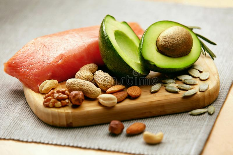 Healthy Fats. Fresh Organic Food On Table. Close Up Of Avocado, Nuts And Salmon Fillet Lying On Wooden Cutting Board In Kitchen. Food Ingredients For Healthy stock photo