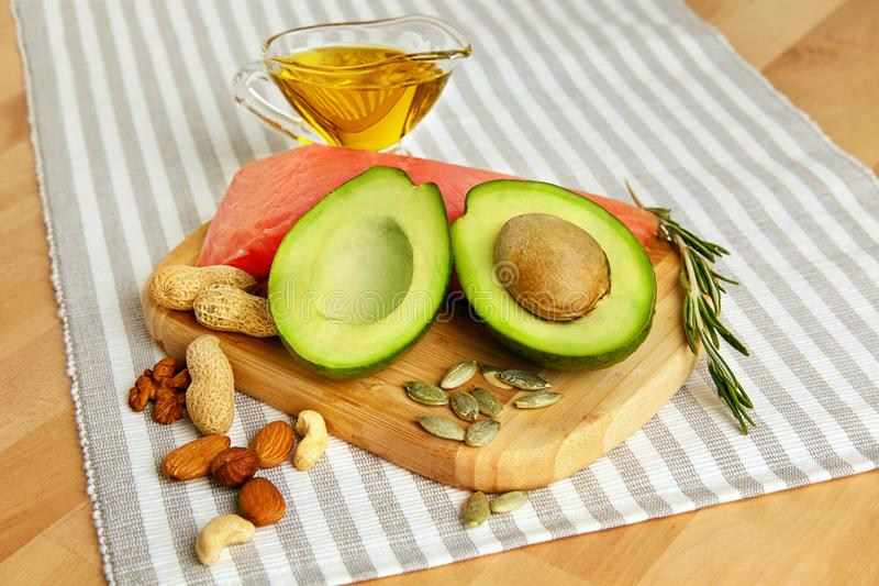 Healthy Fats. Fresh Organic Food On Table. Close Up Of Avocado, Nuts, Olive Oil And Salmon Fillet Lying On Wooden Cutting Board In Kitchen. Food Ingredients royalty free stock photography