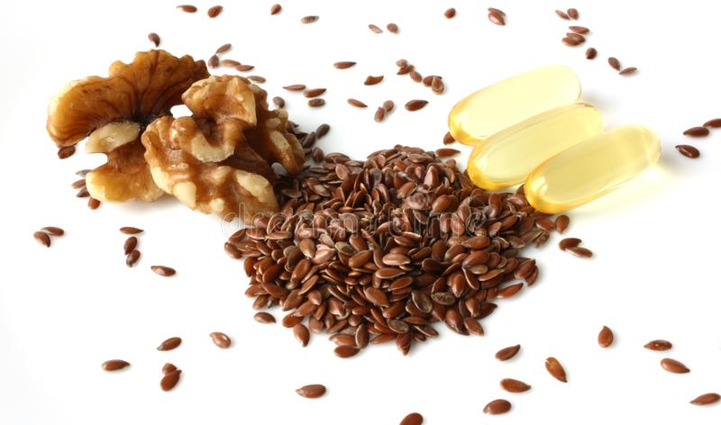 Healthy Fats: Omega-3 Fatty Acids. Three excellent sources of omega-3 fatty acids: walnuts, flax seeds, and fish oil capsules royalty free stock images