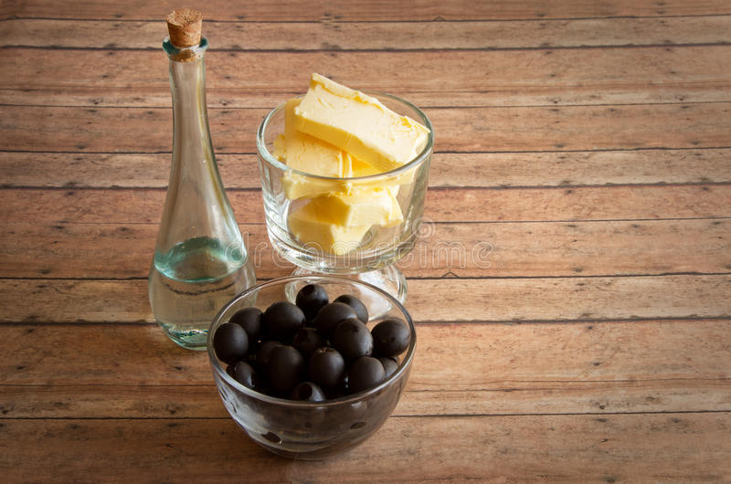Healthy Fats of real butter, Olives and MCT and Coconut oil for. A Ketogenic Diet on a wood plank board stock photography