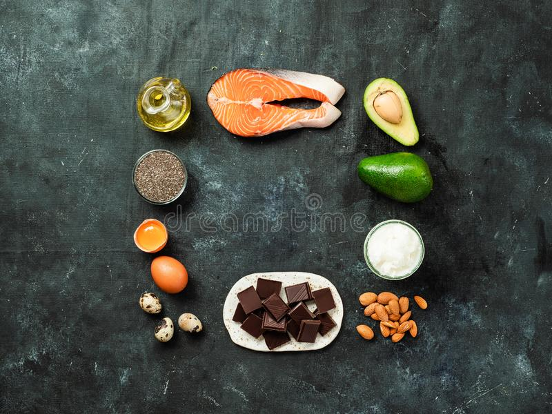 Healthy fats sources concept, copy space, top view. Healthy fats sources concept. Different food ingredients rich good healthy fats on dark background with copy stock image
