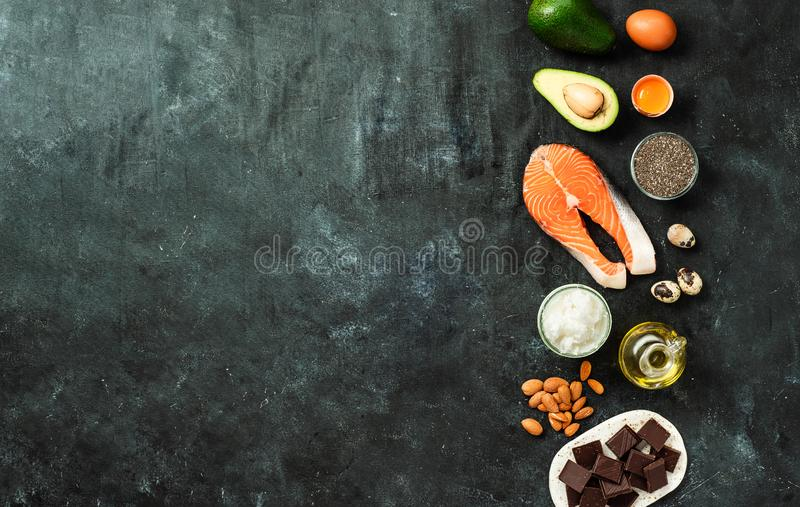 Healthy fats sources concept, copy space, top view. Healthy fats sources concept. Different food ingredients rich good healthy fats on dark background. Copy stock image