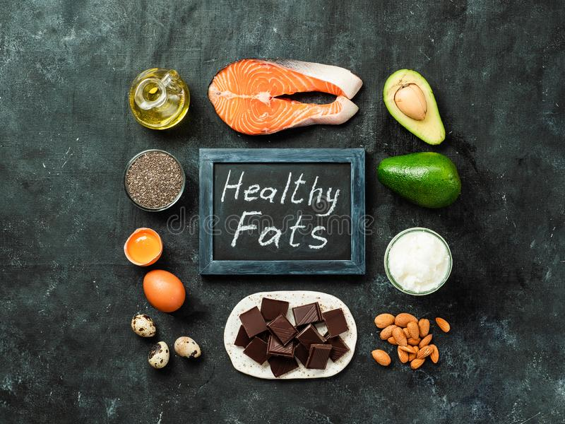 Healthy fats sources concept, top view. Healthy fats sources concept. Different food ingredients and chalkboard with ealthy Fats words on dark background. Top stock photography
