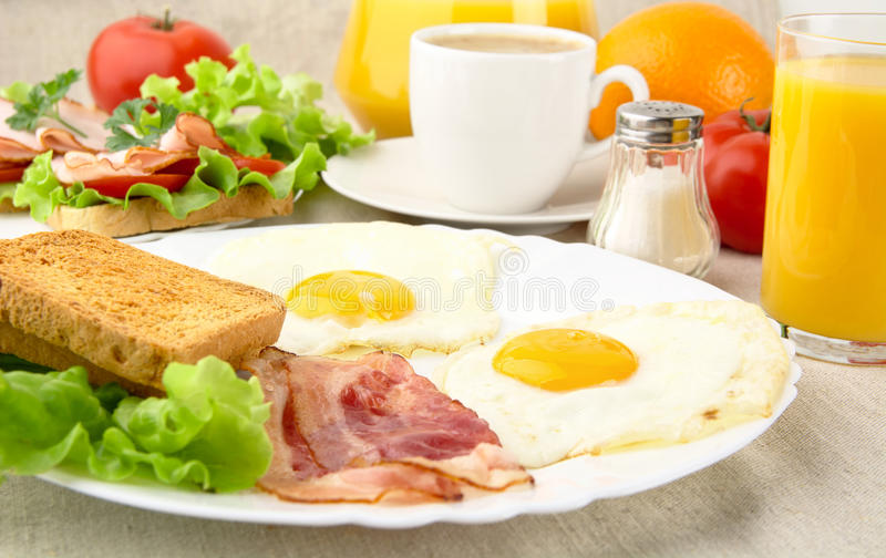 Healthy fatty breakfast with cup of coffee with bacon,eggs. On linen background stock photography