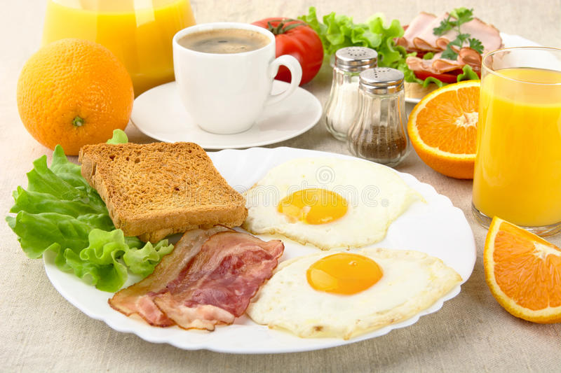 Healthy fatty breakfast with cup of coffee with bacon,eggs. On linen background stock images