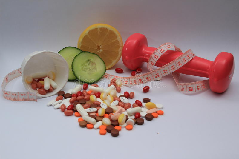 Healthy and fit body. Vitamines and supplements paper cup and healthy food measure tape stock photo