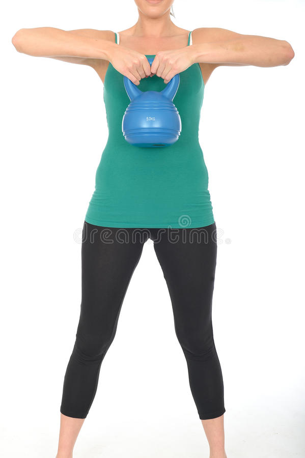 Healthy Fit Young Woman Lifting a 5kg Kettle Bell Weight. A DSLR royalty free image, a healthy fit young woman, lifting a 5kg kettle bell weight, with both hands stock photo