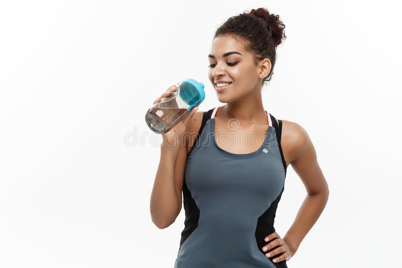 Healthy and Fitness concept - beautiful African American girl in sport clothes drinking water after workout. Isolated on. White studio background royalty free stock images