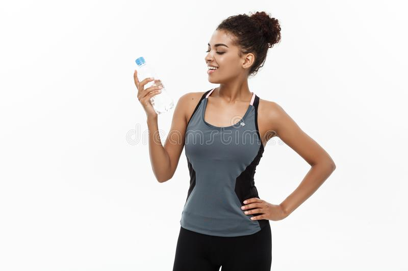 Healthy and Fitness concept - beautiful African American girl in sport clothes holding plastic water bottle after stock photography