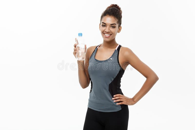 Healthy and Fitness concept - beautiful African American girl in sport clothes holding plastic water bottle after royalty free stock images
