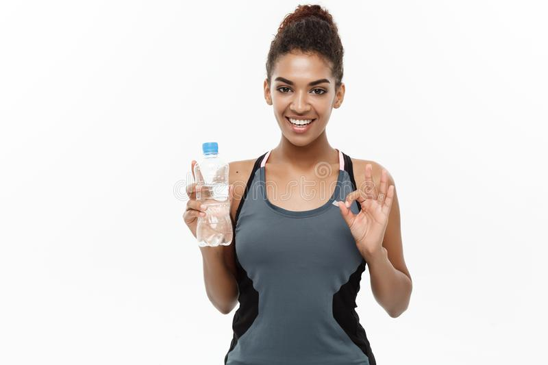 Healthy and Fitness concept - beautiful African American girl in sport clothes holding plastic water bottle after stock photo