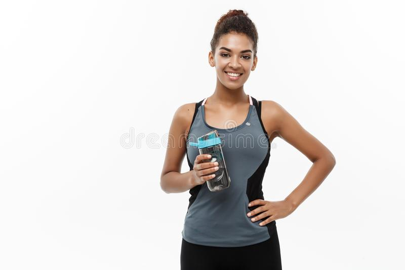 Healthy and fitness concept - beautiful African American girl in sport clothes holding water bottle after workout. Isolated on white studio background royalty free stock photos