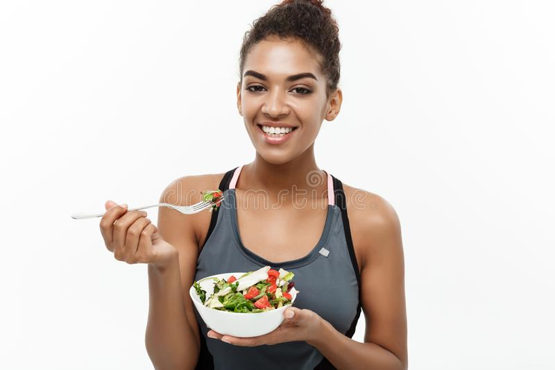 Healthy and Fitness concept - Beautiful American African lady in fitness clothes on diet eating fresh salad. Isolated on. White background royalty free stock photo