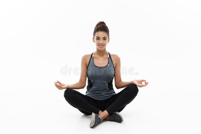 Healthy and Fitness concept - Beautiful American African lady in fitness clothing doing yoga and meditation. Isolated on royalty free stock photography