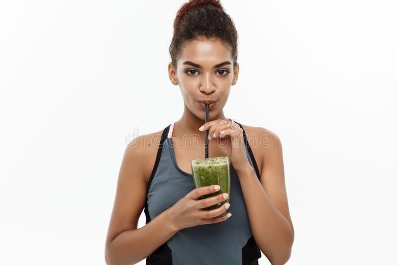 Healthy and Fitness concept - Beautiful American African lady in fitness clothing drinking healthy vegetable drink stock image