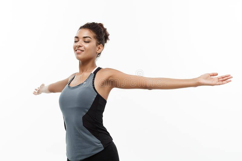 Healthy and Fitness concept - Portrait of young beautiful African American with her hands outstretched and closing eyes stock photography