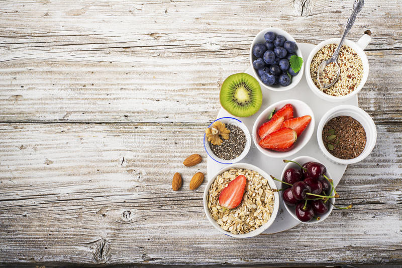 Healthy fitness food from fresh fruits, berries, greens, super food: kinoa, chia seeds, flax seed, strawberry, blueberry royalty free stock photos