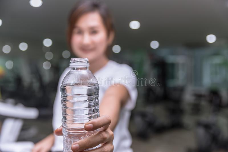 healthy fitness girl smile hand hold give water bottle of drinking water royalty free stock photography