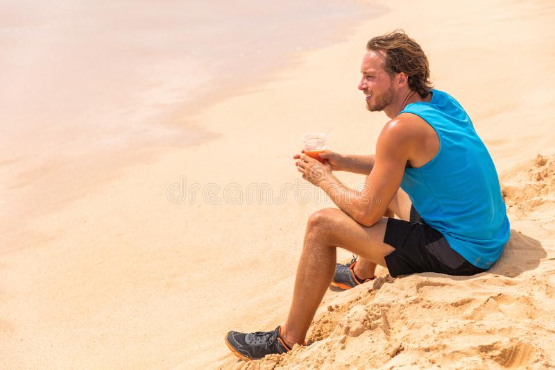 Healthy fitness man drinking detox juice drink on beach run. Runner athlete relaxing on training break with juice smoothie for. Diet royalty free stock image