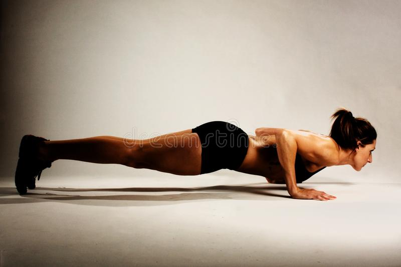 Healthy Fitness Woman doing a Pushup. A healthy fit woman with defined muscles, also a Crossfit athlete stock image