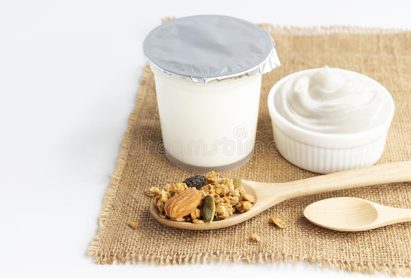 Healthy flavored yogurt in plastic cup and ceramic bowl with cereal and wooden spoon isolated on the white background. With copy. Healthy flavored yogurt in stock images