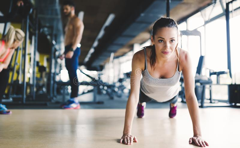 Healthy focused girl doing push ups. In gym royalty free stock images