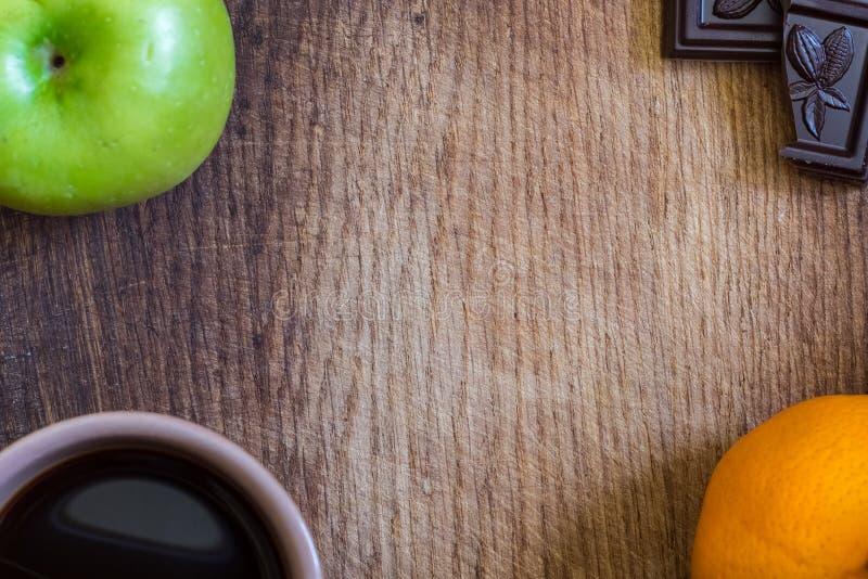 Healthy food. apple, orange, dark chocolate and balck coffe royalty free stock photography