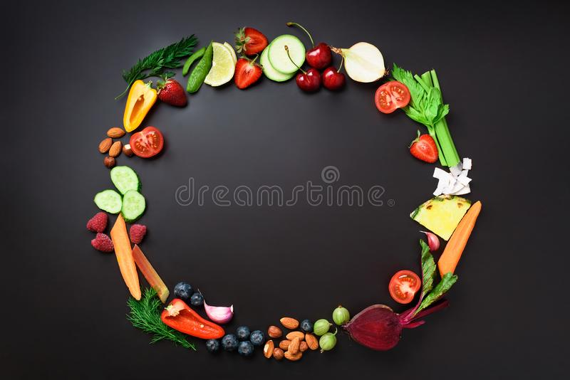 Healthy food background. Circle of organic vegetables, fruits, nuts, berries with copy space on black chalkboard. Top stock image