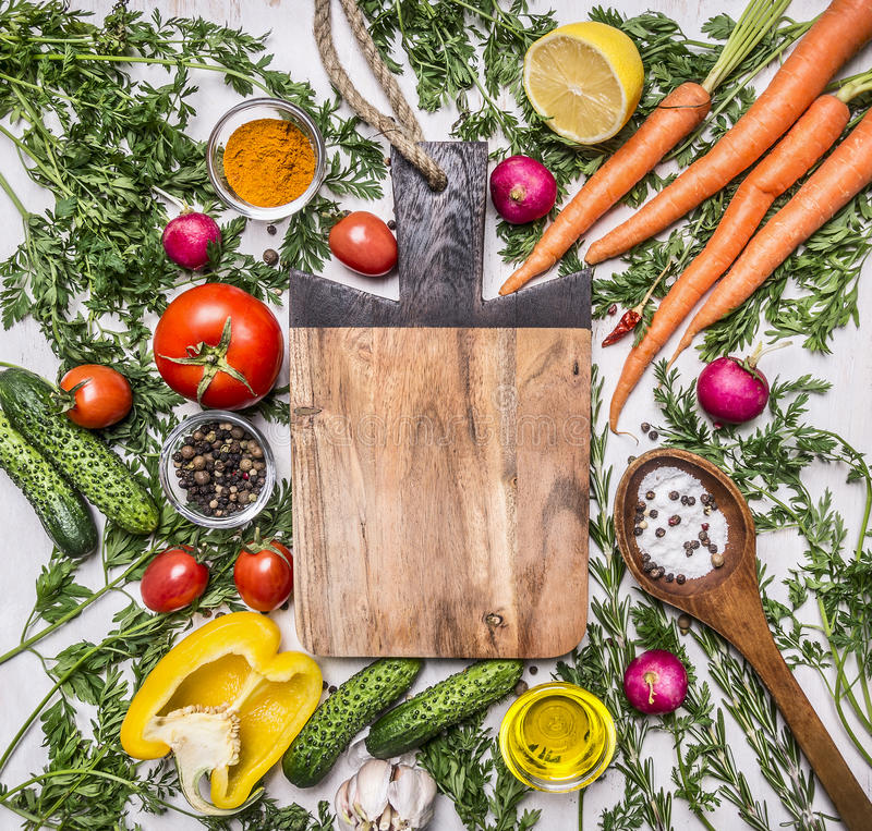 Healthy food background with colorful various vegetables for tasty cooking around the cutting board place for text, frame on woode stock photos