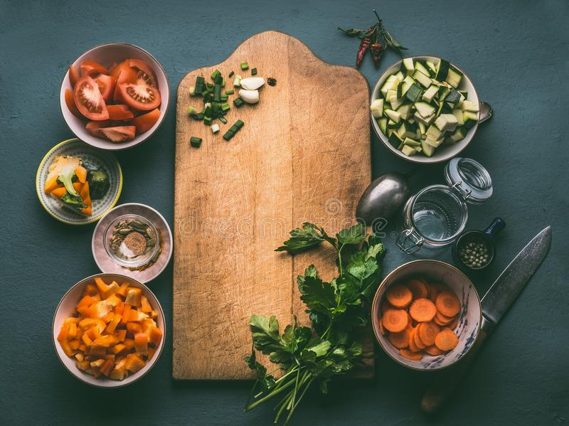 Healthy food background with cutting board, various fresh diced vegetables ingredients, spoon and glass jar for lunch making, top. View, frame. Vegetarian royalty free stock photography
