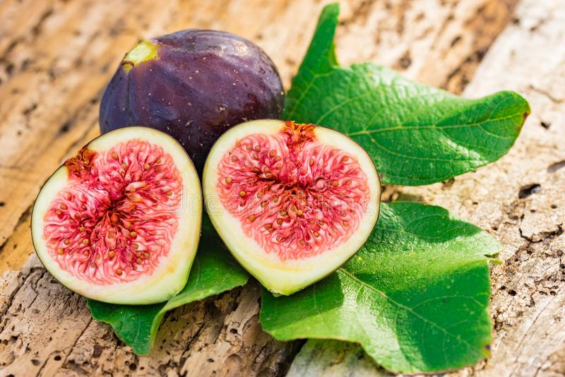 Healthy food background, fresh sliced fig fruits on rusitc wooden table royalty free stock photos