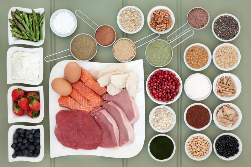 Healthy Food for Body Builders. With meat, salmon, supplement powders, dairy, nuts, seeds, fruit, pulses, herbs, grains and cereals on wooden green background royalty free stock photography