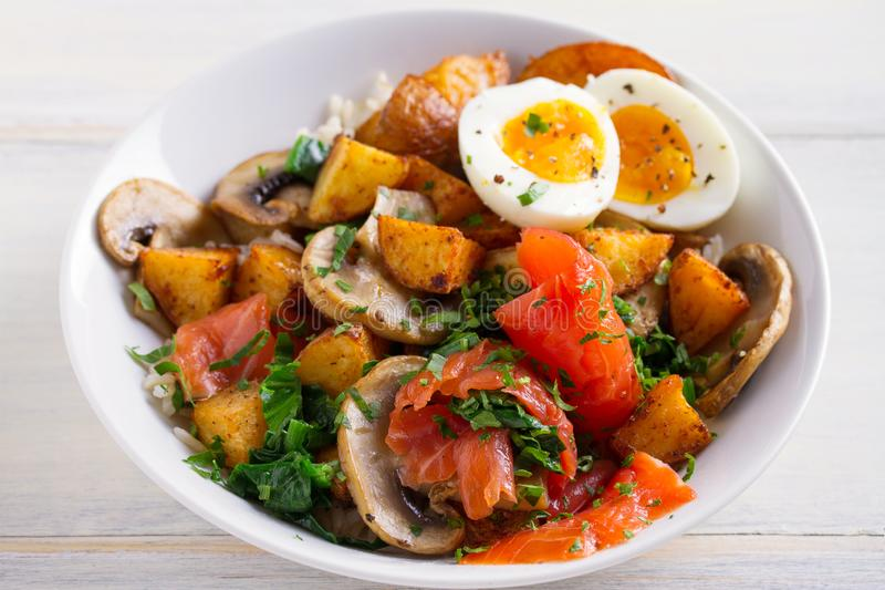 Healthy food bowl: salmon, eggs, potatoes, mushrooms, rice and spinach on white wooden table stock photo