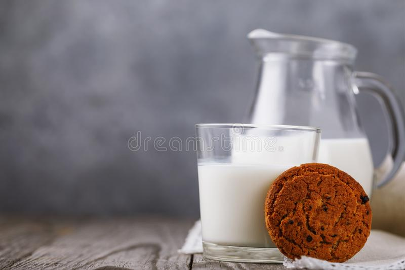 Healthy food for breakfast: milk with oatmeal cookies on a wooden table with copy space stock photography