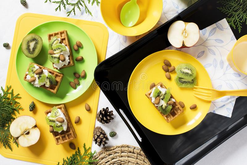 Healthy food. Breakfast with waffles, kiwi, almond, soft cheese, apple, milk on white background. royalty free stock photography