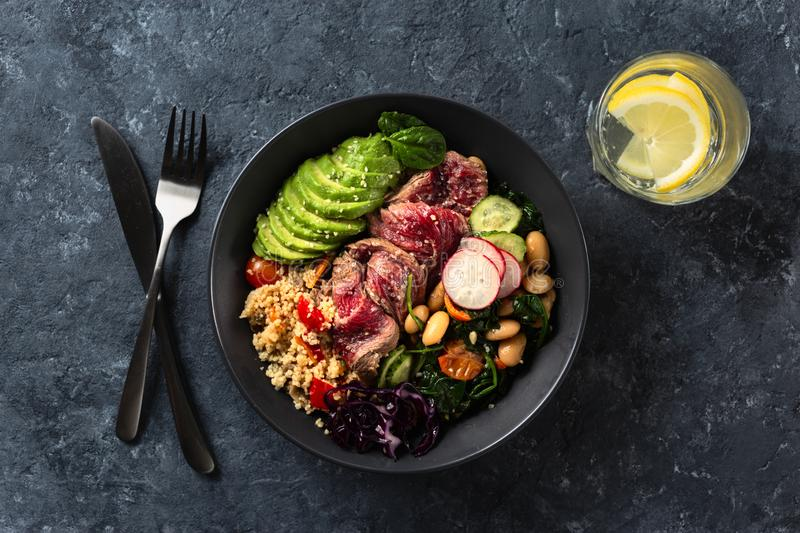 Healthy food buddha bowl with beef steak, beans, couscous, avocado vegetables. Healthy food buddha bowl with beef steak, beans, couscous, avocado and vegetables stock photos